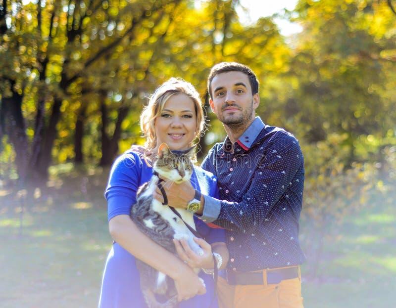 Lyckliga och för barn gravida par som kramar i natur arkivbilder