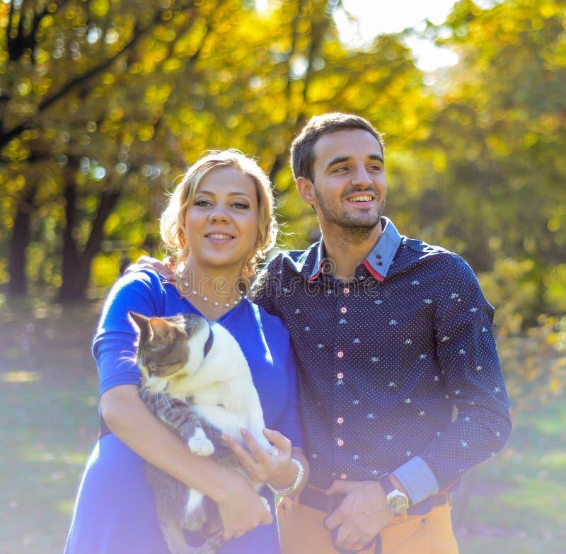 Lyckliga och för barn gravida par som kramar i natur royaltyfri foto