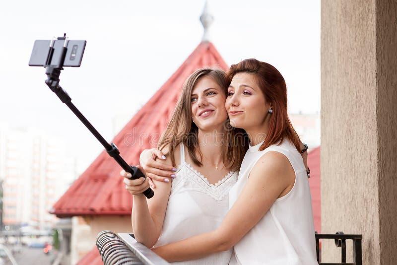 Lyckliga och positiva kvinnliga vänner som tar en selfie royaltyfria foton