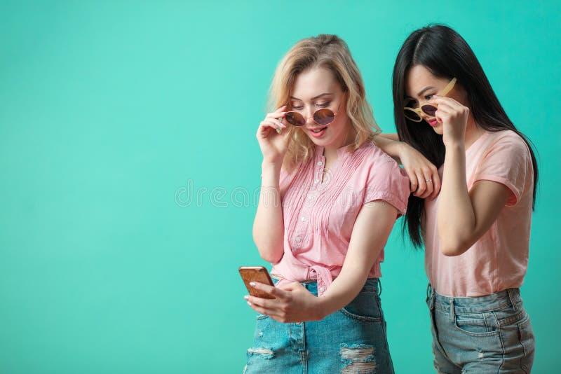 Lyckliga olika unga flickor som tar selfie med smartphonen mot den blåa väggen fotografering för bildbyråer