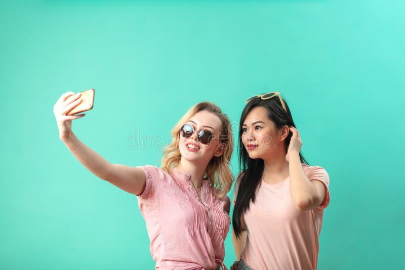 Lyckliga olika unga flickor som tar selfie med smartphonen mot den blåa väggen royaltyfria foton
