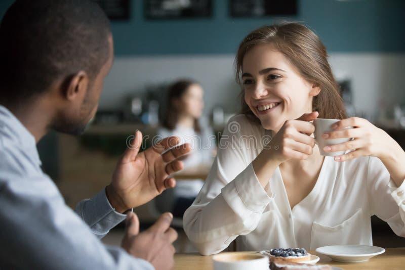 Lyckliga olika vänner talar ha roligt möte i kafé royaltyfri foto