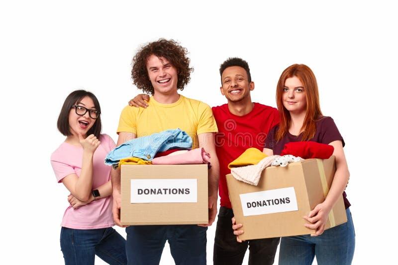 Lyckliga olika volontärer med donationer arkivfoto