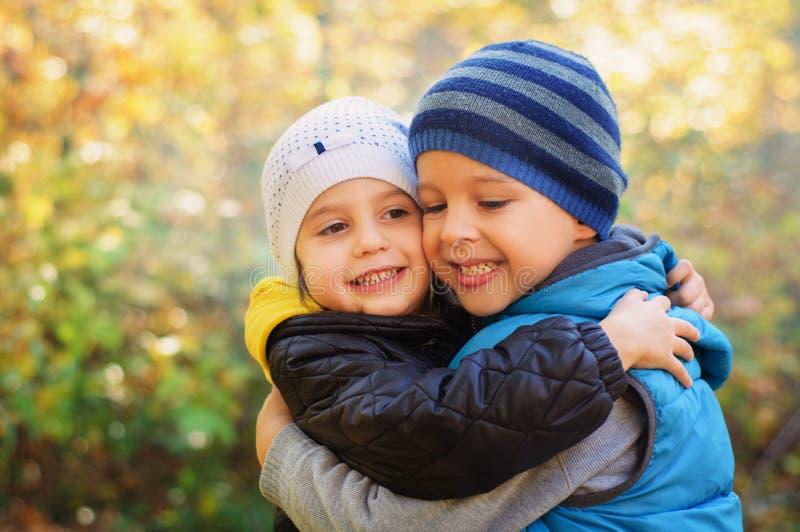 Lyckliga omfamna barn royaltyfria foton