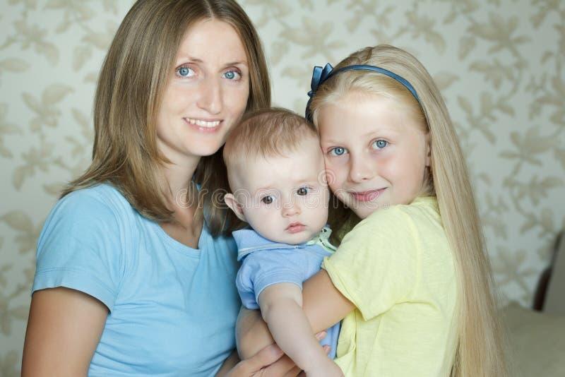 Lyckliga omfamna familjemedlemmar som poserar för inomhus stående fotografering för bildbyråer