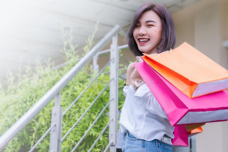 Lyckliga påsar för kvinnaleende- och innehavsändnings som shoppar på dagen royaltyfri foto