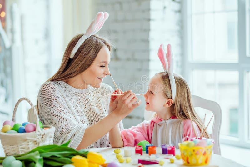 Lyckliga påskförberedelser Mamman och dottern förbereder sig för påsk tillsammans På tabellen är en korg med påskägg, blommor royaltyfria bilder