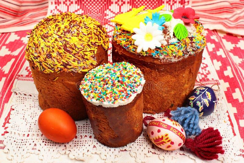 Lyckliga påskkakor och målade ägg med ordKristus har uppstiget royaltyfri fotografi