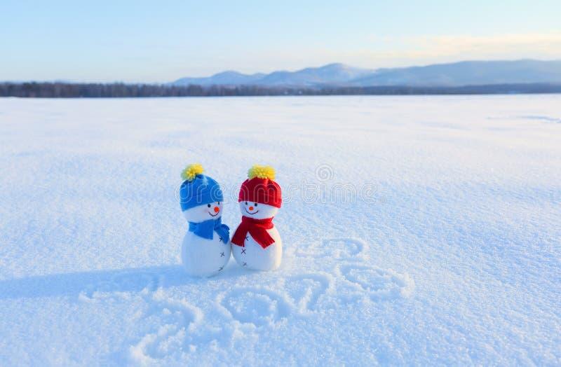 Lyckliga par av det förälskade anseendet för snögubbe på snön Blå röd hatt och halsduk Handstilar 2019 Liggande med berg arkivfoto