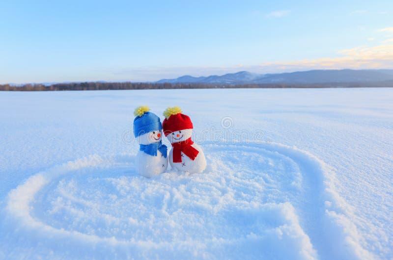 Lyckliga par av det förälskade anseendet för snögubbe på snön Målad hjärta Handstilar 2019 Liggande med berg royaltyfri fotografi