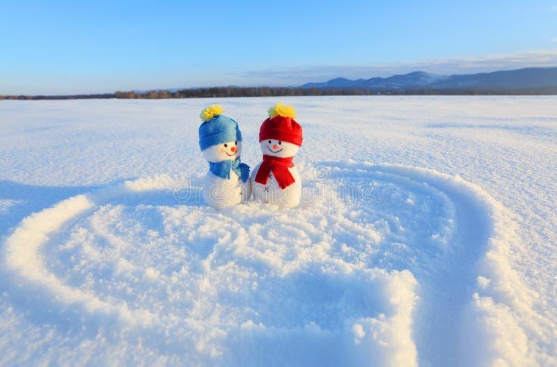 Lyckliga par av det förälskade anseendet för snögubbe på snön Målad hjärta Handstilar 2019 Liggande med berg royaltyfria foton