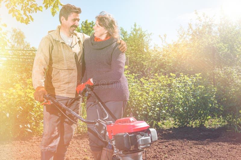 Lyckliga par av en familj av bönder på deras trädgård jublar på a arkivfoto