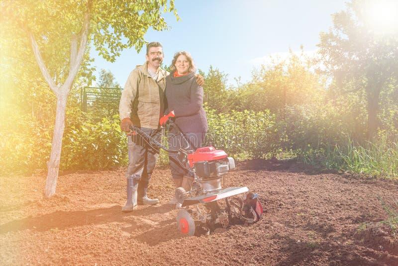Lyckliga par av en familj av bönder på deras trädgård jublar på a royaltyfria bilder