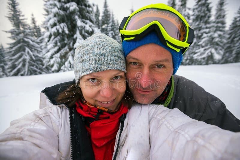 Lyckliga par av handelsresande som tar selfie i vinterbergen royaltyfri fotografi