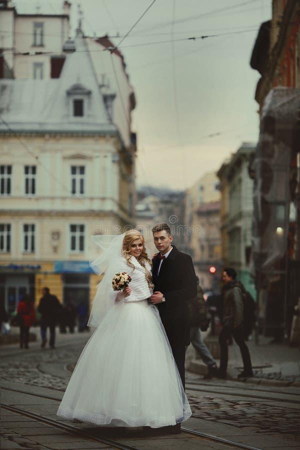 Lyckliga par av nygift personvalentynes som poserar i gammal europeisk stree arkivbilder
