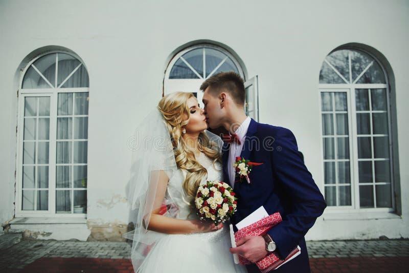 Lyckliga par av nygifta personer som förutom kysser registrering medan håll royaltyfri fotografi