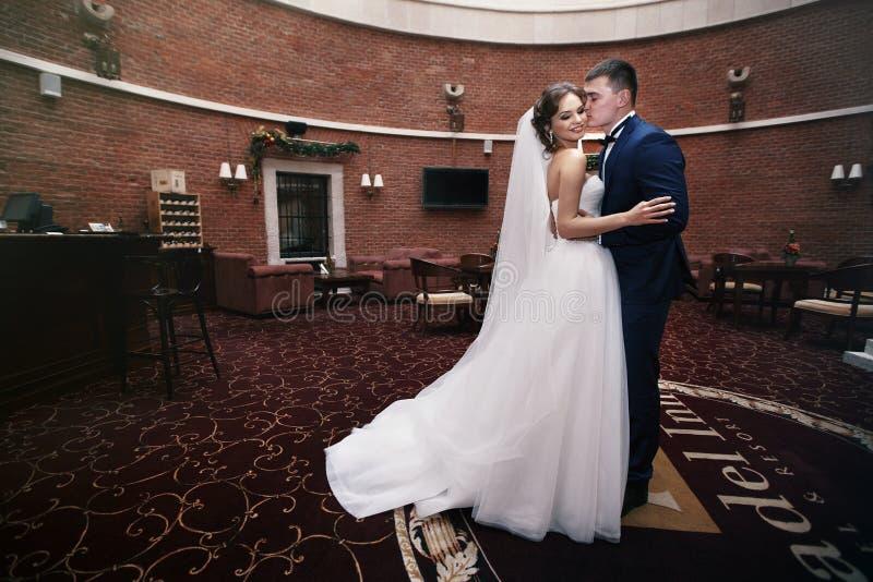 Lyckliga par av nygifta personer som kramar i lyxig mottagandekorridor arkivbilder
