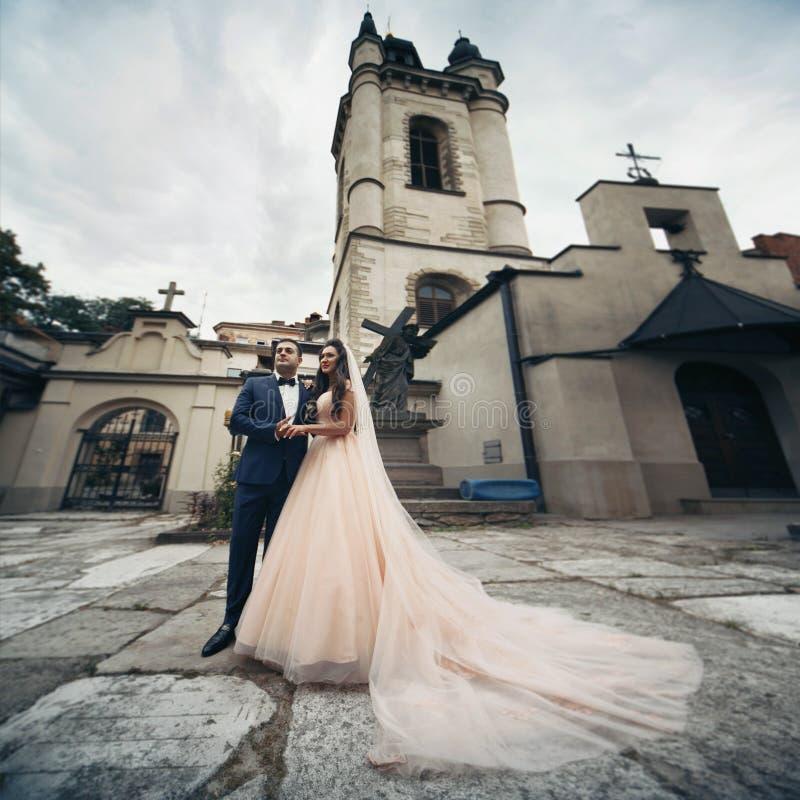 Lyckliga par av nygifta personer som rymmer händer med en gammal kyrka i Lv arkivfoto