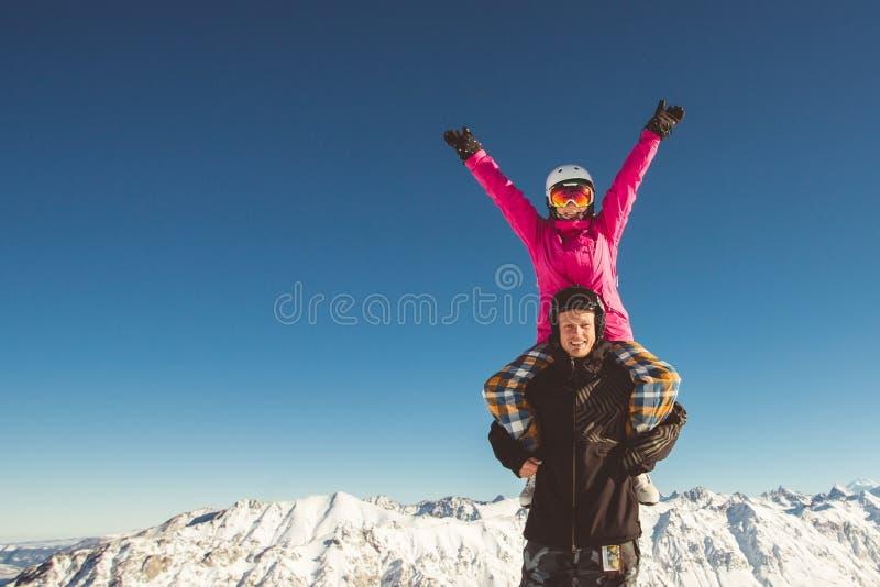 Lyckliga par av snowboarders i de alpina bergen royaltyfria foton