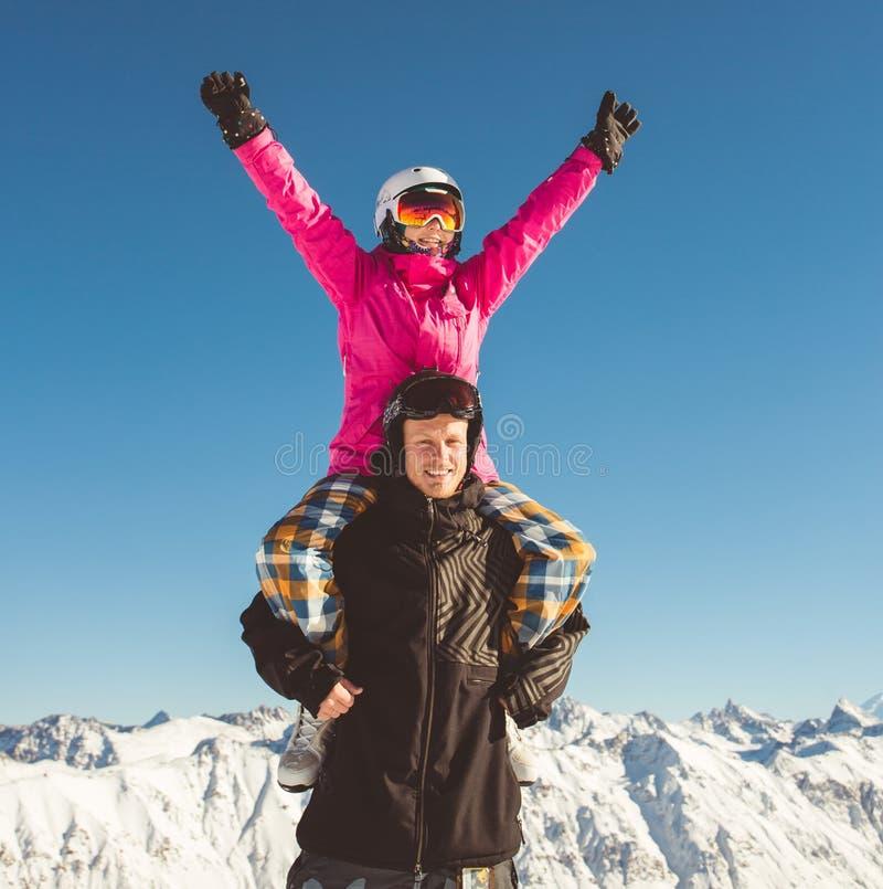 Lyckliga par av snowboarders i de alpina bergen royaltyfri fotografi