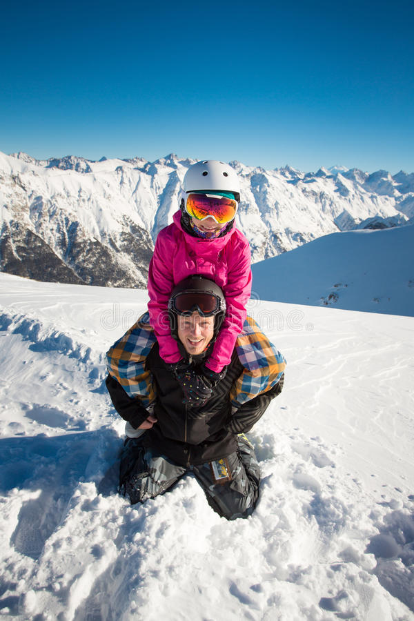 Lyckliga par av snowboarders i de alpina bergen royaltyfri bild