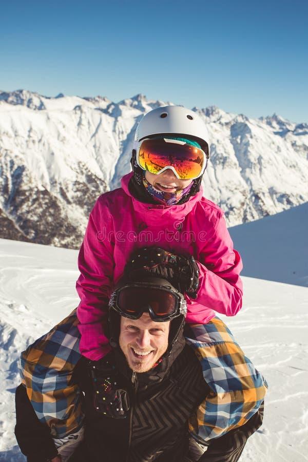 Lyckliga par av snowboarders i de alpina bergen fotografering för bildbyråer