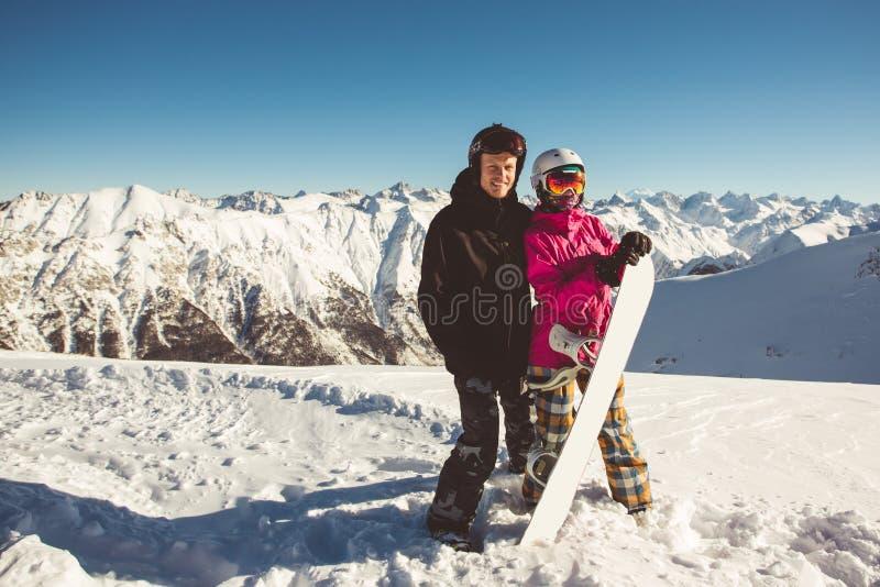 Lyckliga par av snowboarders i de alpina bergen arkivbilder