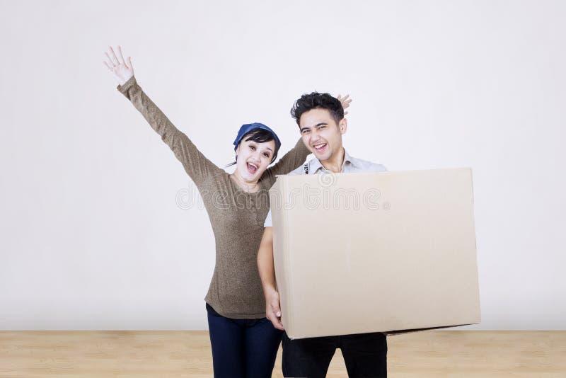 Lyckliga par bär asken hemma royaltyfria bilder