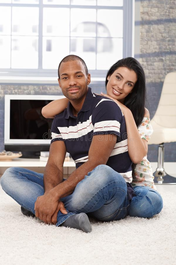 Lyckliga par för blandad race hemma royaltyfri fotografi