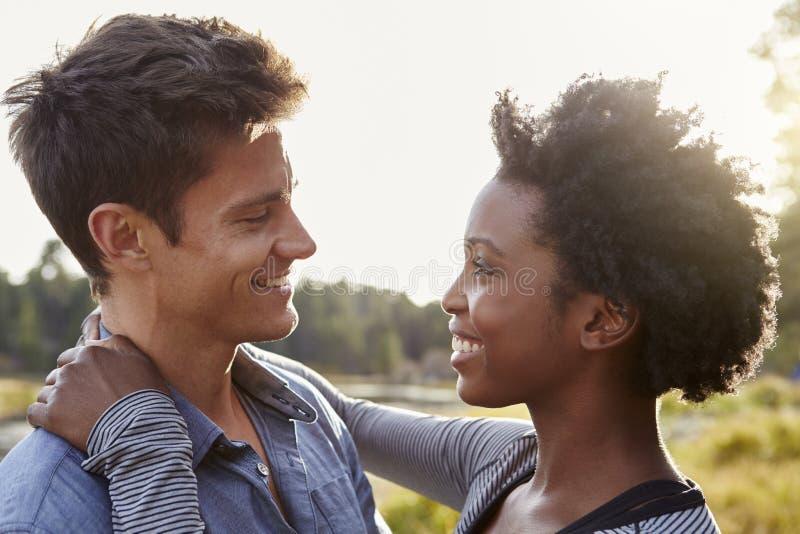 Lyckliga par för blandat lopp som omfamnar i bygden royaltyfri foto