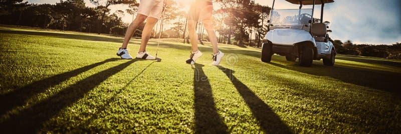 Lyckliga par för golfspelare som ger höjdpunkt fem royaltyfri fotografi