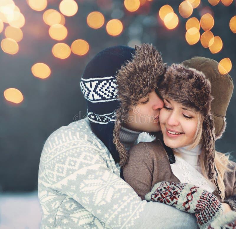 Lyckliga par för ståendenärbild i vinterdag, försiktig kyssa kvinna för man i hatten, stucken tröja, arkivbilder