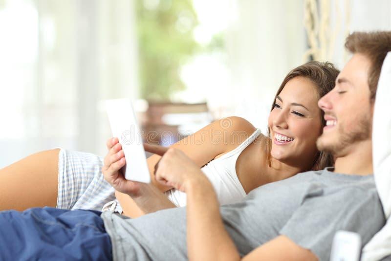 Lyckliga par genom att använda en minnestavla som ligger på sängen royaltyfri foto