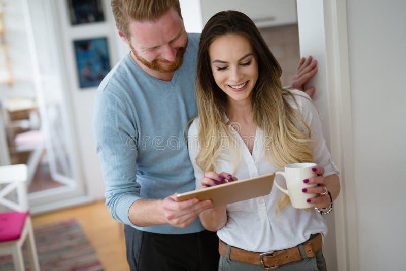 Lyckliga par genom att använda minnestavlan och dricka kaffe hemma arkivfoton