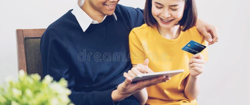 Lyckliga par genom att anv?nda minnestavlan och kreditkorten med shopping direktanslutet tillsammans hemma fotografering för bildbyråer
