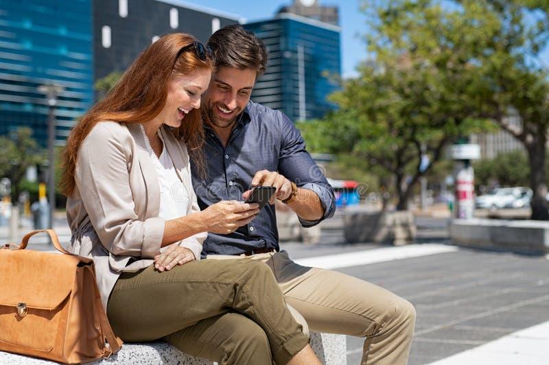 Lyckliga par genom att använda smartphonen i stadsmitt arkivfoton