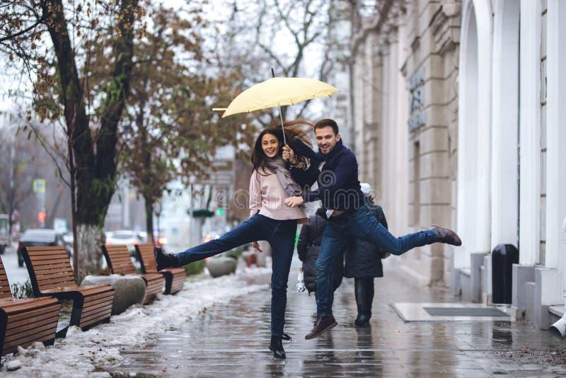 Lyckliga par, grabben och hans iklädda tillfälliga kläder för flickvän hoppar under paraplyet på gatan i regnet arkivbild