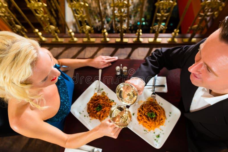 Lyckliga par har ett romantiskt datum i restaurang arkivfoto