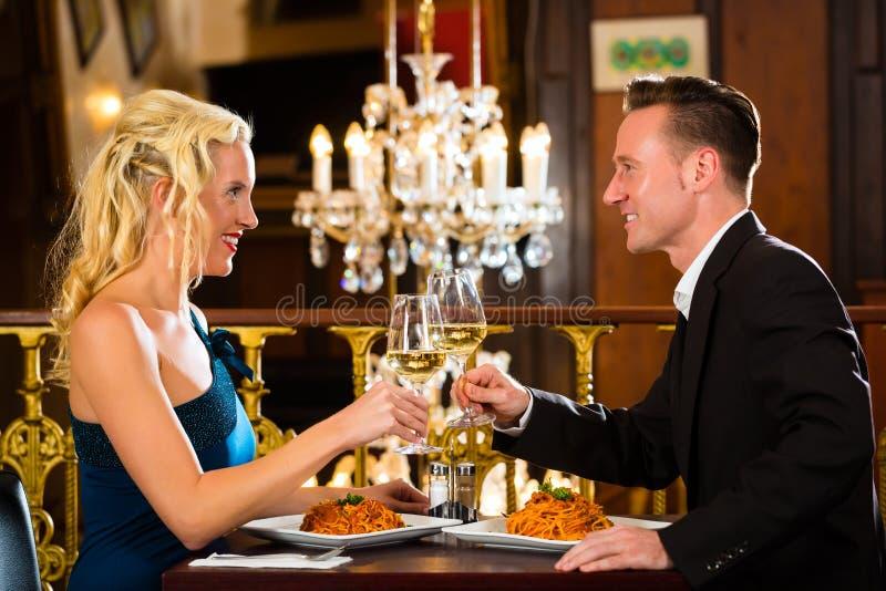 Lyckliga par har ett romantiskt datum i restaurang arkivfoton