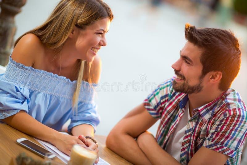 Lyckliga par har gyckel i kafé fotografering för bildbyråer