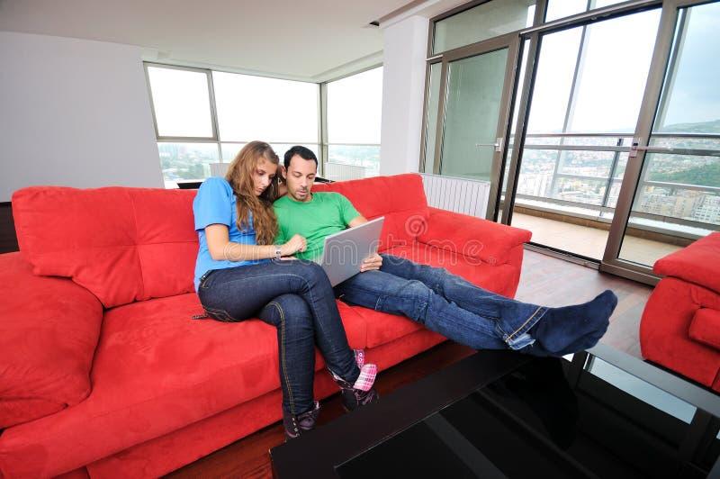 Lyckliga par har gyckel och arbete på bärbar dator hemma arkivfoton