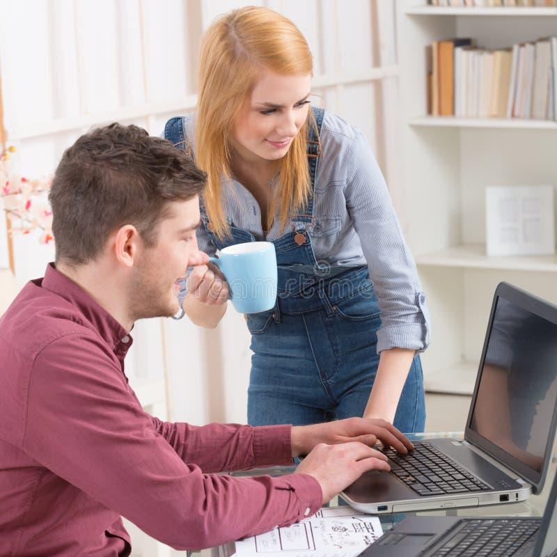 Lyckliga par hemma med bärbar datordatoren arkivbild