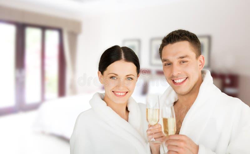 Lyckliga par i badrockar över brunnsorthotellrum arkivfoto