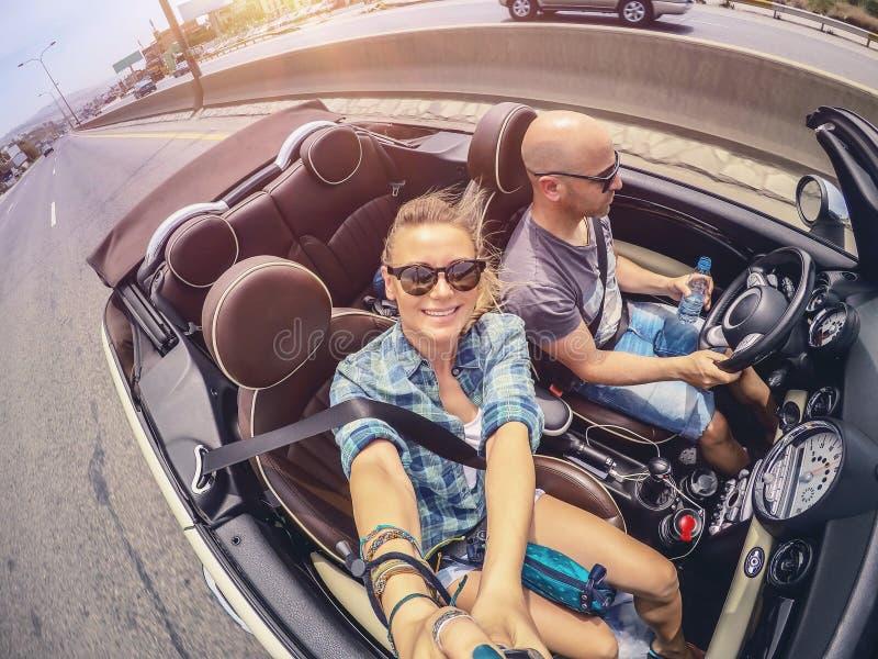 Lyckliga par i bilen arkivfoton