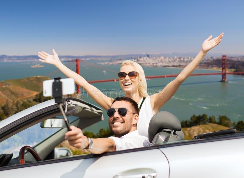 Lyckliga par i bilen som tar selfie vid smartphonen royaltyfri bild