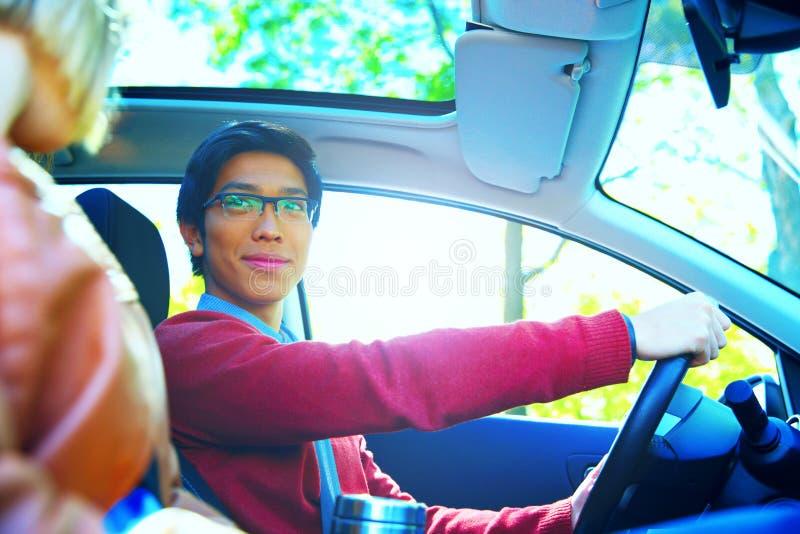 Lyckliga par i en bil med solen som skiner royaltyfri foto