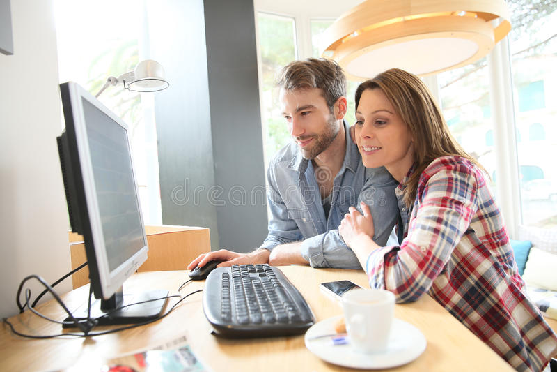 Lyckliga par i en cybercafe som websurfing royaltyfri fotografi