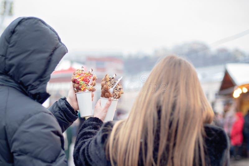 lyckliga par i för ätabubbla för varm kläder förälskade dillandear på julmässan ferie-, vinter-, jul- och folkbegrepp royaltyfria foton