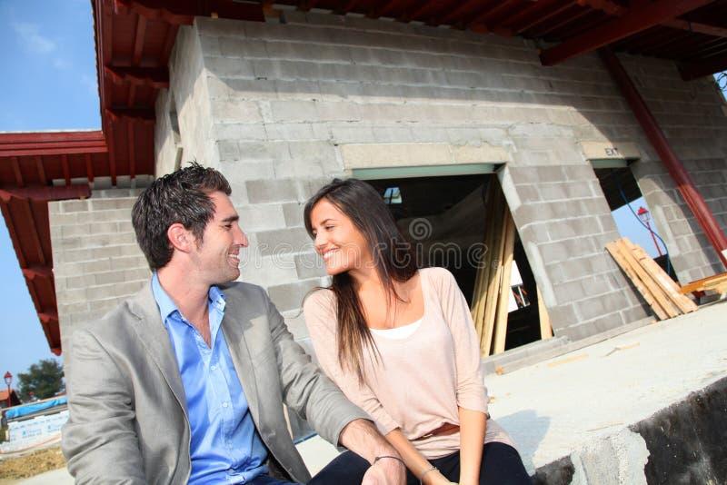Lyckliga par i hus under konstruktion arkivbilder