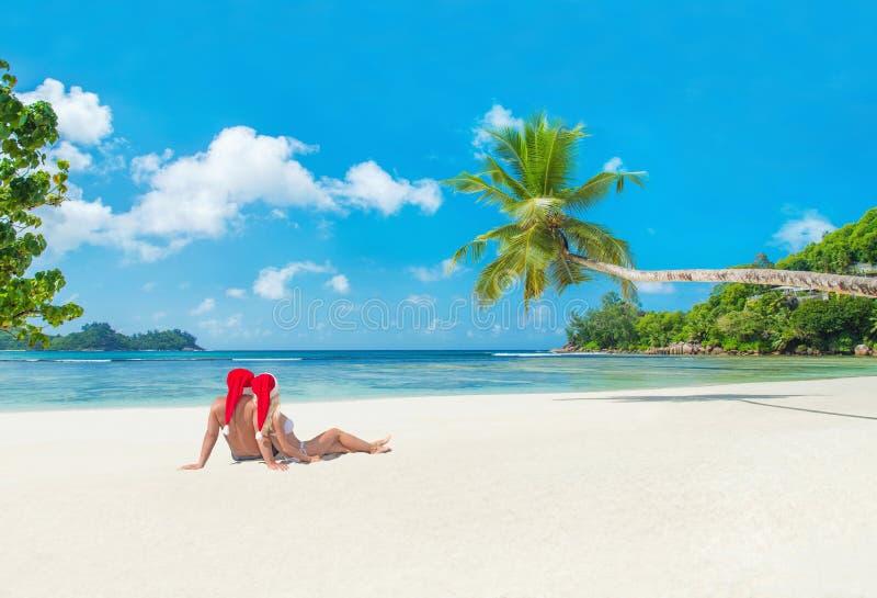 Lyckliga par i julhattar på tropiska sandiga Palm Beach royaltyfria foton